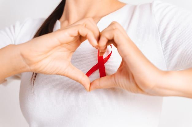 Primo piano della mano della donna a forma di cuore con il nastro rosso del distintivo sul petto per sostenere la giornata dell'aids. concetto di consapevolezza sanitaria, medicina e aids.