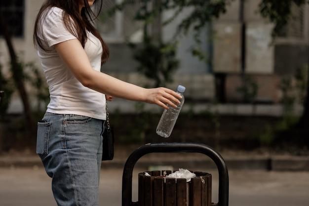 Primo piano della mano della donna che getta la bottiglia di acqua vuota di plastica nella spazzatura di legno. concetto di riciclaggio.