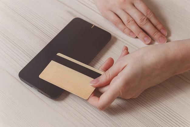 Telefono di uso della mano della donna del primo piano e carta di credito sulla tavola.