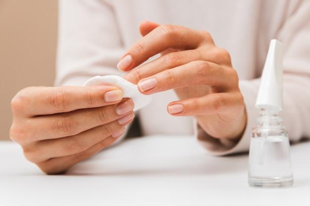 Mani della donna del primo piano che rimuovono pittura dalle unghie con il cuscinetto di cotone