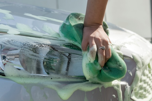 Mani della donna del primo piano usando una spugna verde con schiuma di sapone che lava la sua automobile moderna