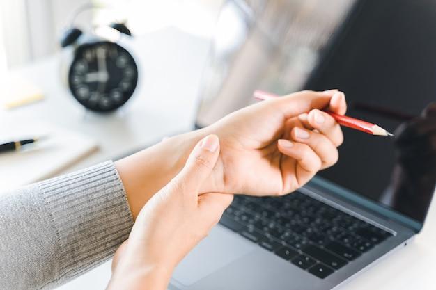 Donna del primo piano che tiene il suo dolore al polso dall'uso del computer da molto tempo. concetto di sindrome dell'ufficio.