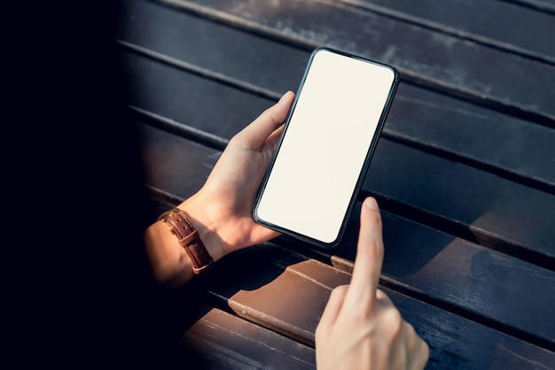 Primo piano della donna che tiene uno smartphone, dello schermo in bianco. usando il cellulare sul caffè. tecnologia per il concetto di comunicazione.