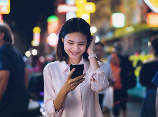 Primo piano della donna che tiene uno smartphone alla notte sulla strada dei negozi della città e la gente cammina.