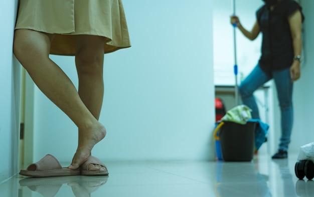 La gamba della donna del primo piano con i capelli ha bisogno della depilazione laser e del trattamento della pelle donna con le gambe pelose sta in piedi