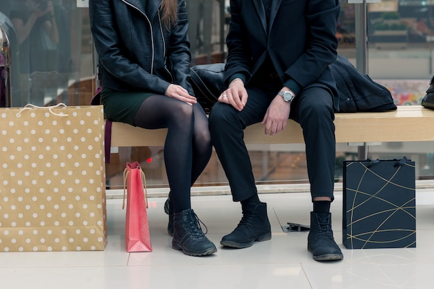 Primo piano di donna e uomo in panchina con colorate shopping bag