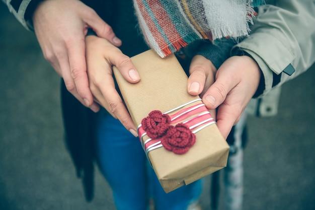 Primo piano delle mani dell'uomo e della donna che mostrano una confezione regalo con fiori rossi fatti a mano all'aperto in una fredda giornata autunnale. amore e concetto di relazioni di coppia.