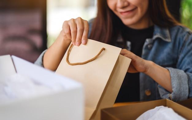 Primo piano di una donna che si apre e che guarda il sacchetto della spesa interno a casa per la consegna e il concetto online di acquisto