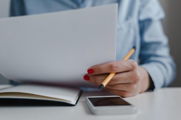 Primo piano della mano della donna con le unghie rosse con la matita sitiing allo scrittorio che tiene i documenti.