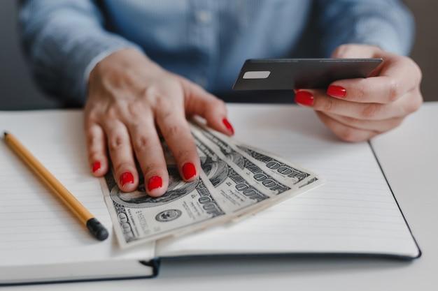 Primo piano delle mani della donna con i chiodi rossi che tengono le banconote dei soldi dei cento dollari e una carta di credito nera