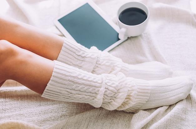 Primo piano delle gambe della donna sul letto. la giovane donna gode del suo soggiorno a casa.
