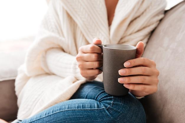 Primo piano della donna seduta e tenendo una tazza di caffè sul divano a casa