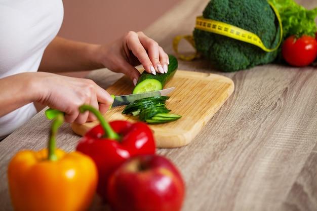 Il primo piano della donna affetta il cetriolo per insalata fresca