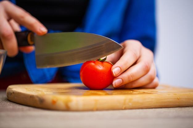 Il primo piano della donna affetta il pomodoro per insalata fresca