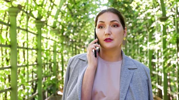 Donna del primo piano che parla al telefono in un arco del giardino