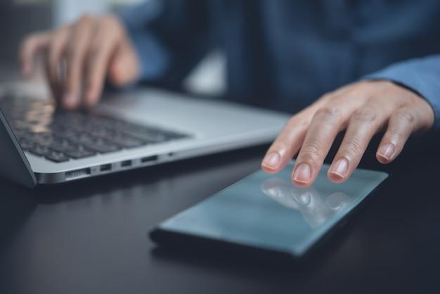 Primo piano della donna che utilizza il telefono cellulare e lavora al computer portatile in ufficio