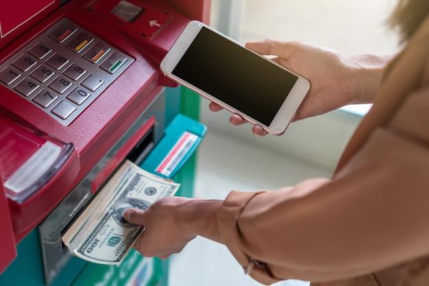 Donna del primo piano che utilizza il telefono cellulare astuto per ritirare i contanti