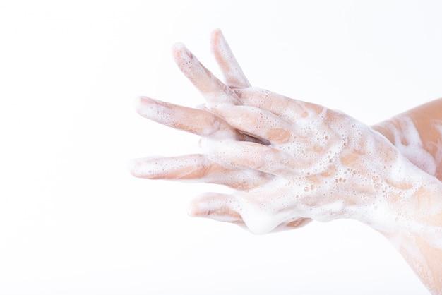 Mani di lavaggio della donna del primo piano con sapone su fondo bianco