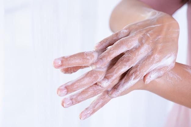 Mani di lavaggio della donna del primo piano con sapone su fondo bianco.