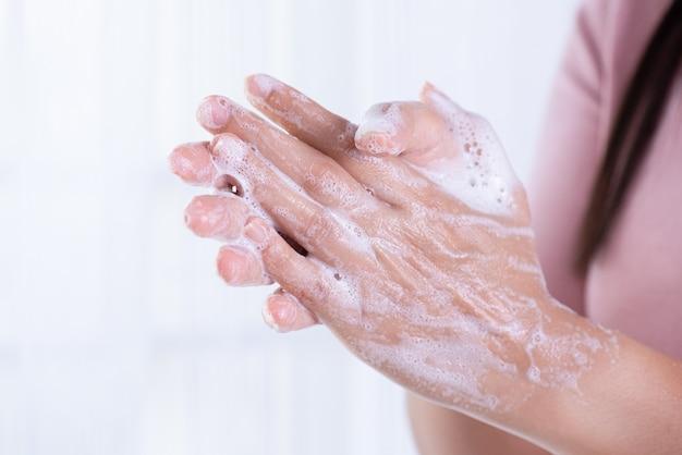 Mani di lavaggio della donna del primo piano con sapone.
