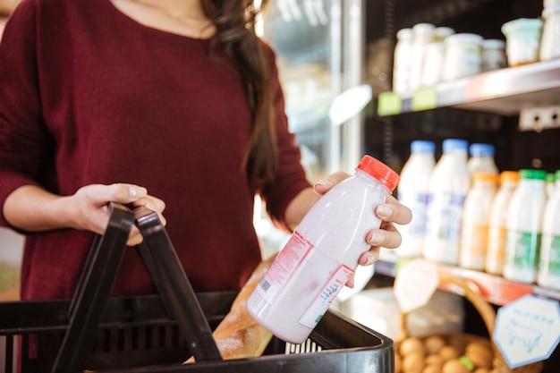 Primo piano della donna con cesto che acquista prodotti lattiero-caseari nel negozio di alimentari