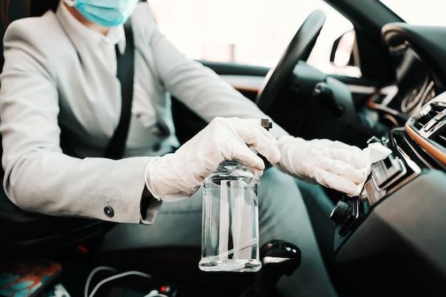Primo piano della donna con la maschera per il viso con guanti di gomma che disinfettano la sua auto con alcool durante l'epidemia di virus corona.