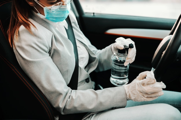 Primo piano della donna con maschera facciale con guanti di gomma sul volante di spruzzatura con alcool e disinfettare la sua auto durante l'epidemia di virus corona.