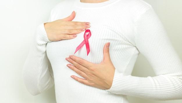 Primo piano della donna con nastro rosa come simbolo di consapevolezza del cancro. sostenere il cancro al seno e il concetto di pazienti con tumore