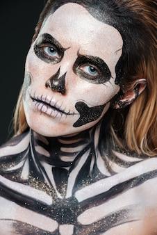 Primo piano di donna con trucco gotico spaventato su sfondo nero