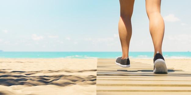 Primo piano delle gambe della donna che cammina sul percorso di legno sulla spiaggia
