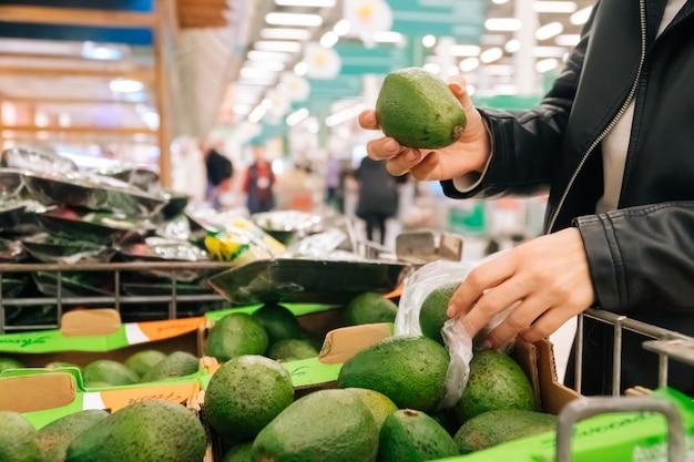 Le mani delle donne del primo piano tengono le drogherie nel deposito. il concetto di acquisto di frutta e verdura in un ipermercato durante la quarantena