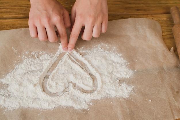 Primo piano le mani delle donne disegnano un cuore dalla farina pubblicità di una panetteria o di una pasticceria