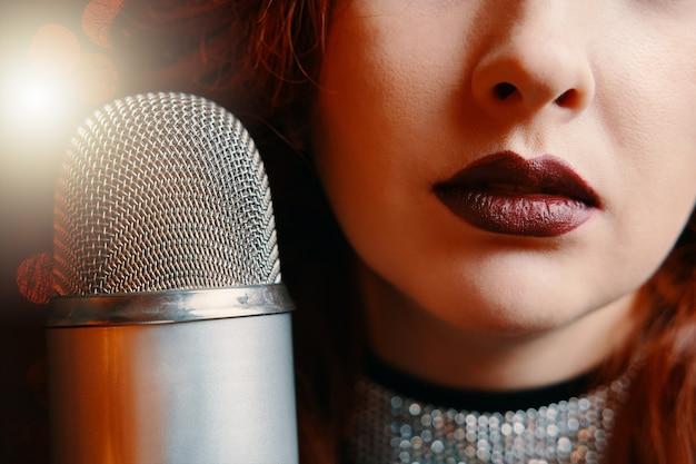 Primo piano delle labbra delle donne dipinte con rossetto bordeaux e cantante microfono retrò con discoteca ...