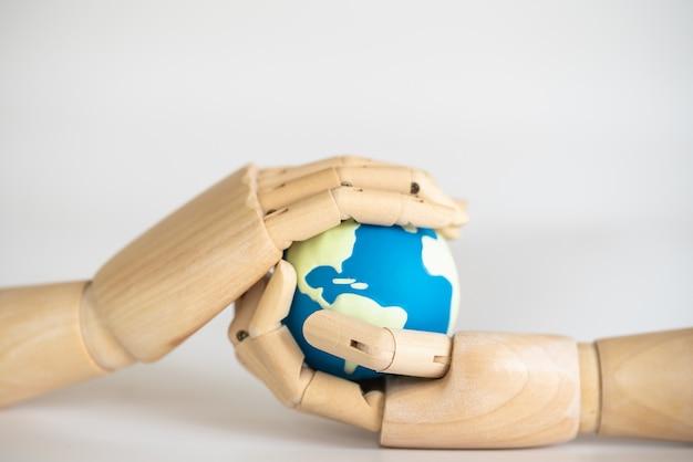 Primo piano della mano di legno che tiene la mini sfera del mondo su bakcgorund bianco.