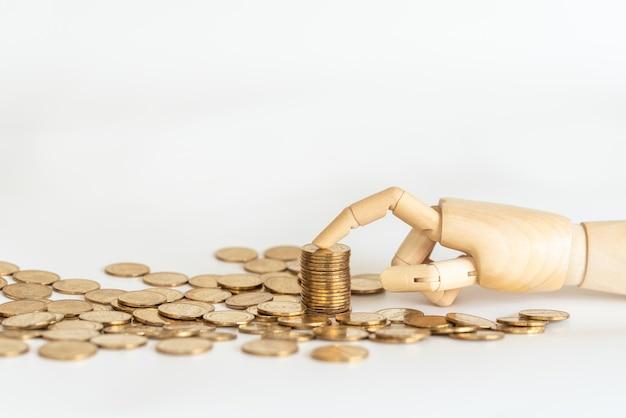 Primo piano del punto del dito di modello della mano di legno alla parte superiore della pila di monete di oro con il mucchio di moneta su bianco.