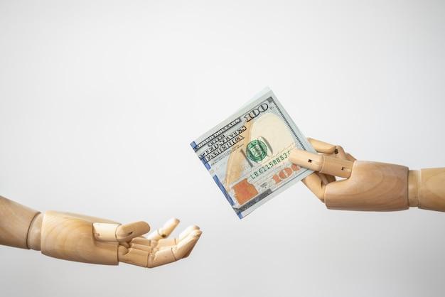 Primo piano della mano in legno modello holding e dare dollari usa
