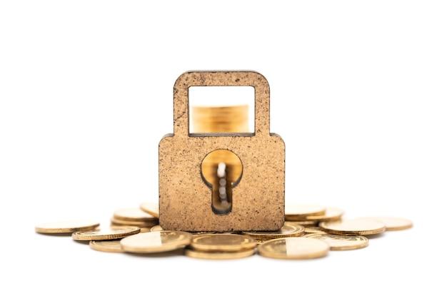 Primo piano dell'icona del lucchetto a chiave principale in legno con pila e pila di monete d'oro su sfondo bianco