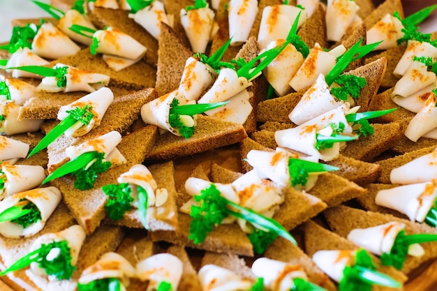 Un primo piano di un piatto di legno con panini appetitosi pane nero e lardo