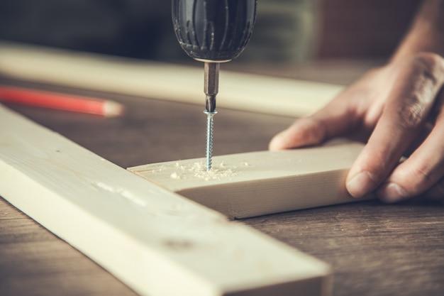 Primo piano della mano del lavoratore di perforazione con il legno