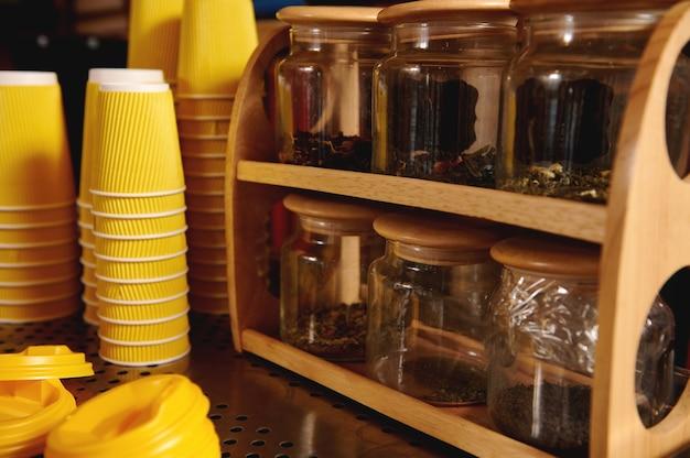 Primo piano di tazze di cartone giallo capovolto su una macchina per il caffè e contenitori di bicchieri trasparenti con tè