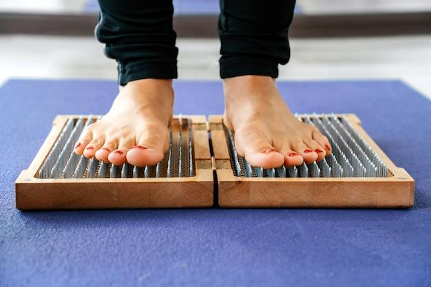 Primo piano della persona di yoga in piedi su una tavola di sadhu con chiodi affilati
