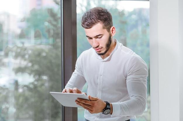 Primo piano di giovane uomo di etnia araba utilizzando tablet pc indoor.