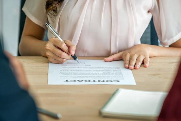 Primo piano giovane donna asiatica laureata a mano che firma il contratto dopo l'intervista dell'affare