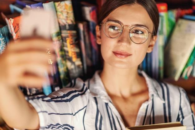 Primo piano di giovane bella bruna in piedi in libreria, tenendo in mano un libro e prendendo un selfie.