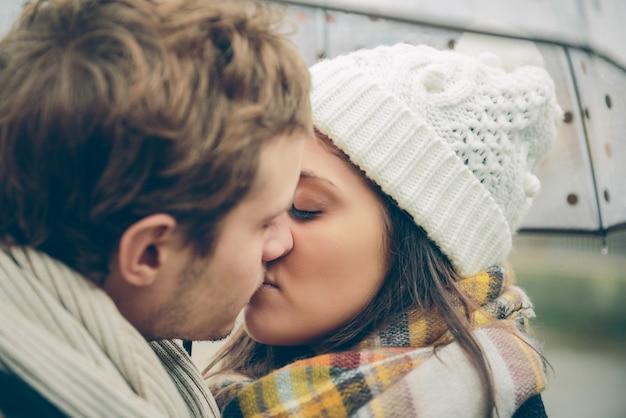Primo piano di giovane bella coppia che si bacia sotto l'ombrellone in una giornata di pioggia autunnale. amore e concetto di relazioni di coppia.