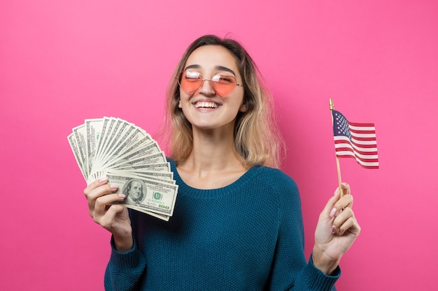 Primo piano di giovane bella donna in un maglione blu in vetri con soldi e bandiera dei dollari americani
