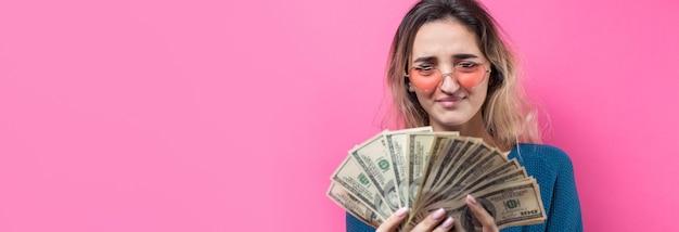 Primo piano di giovane bella donna in un maglione blu in bicchieri con soldi di dollari americani in mano