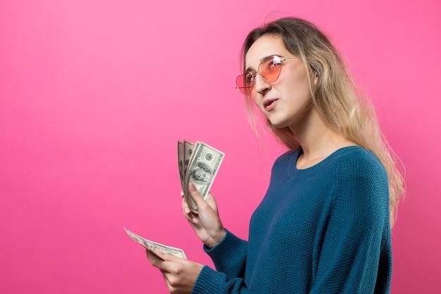 Primo piano di giovane bella donna in un maglione blu in vetri con soldi dei dollari americani