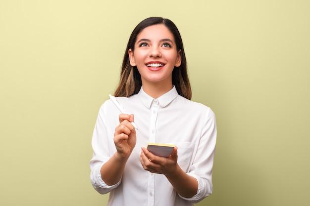 Giovane donna di affari allegra del primo piano con la bella penna di tenuta sana di sorriso che fa le note e che cerca contro il fondo giallo