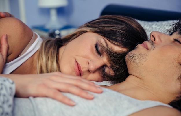 Primo piano di una giovane coppia che dorme abbracciata a letto a casa